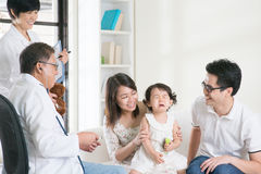 Child vaccines. Child vaccination. Family doctor giving injection or vaccines to baby girl. Pediatrician and patient Stock Image