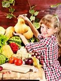 Child with vegetable on kitchen. Stock Photo