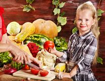 Child with vegetable on kitchen. Stock Photos