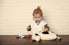 Child veterinarian cure toy animal with vaccine. Boy doctor make injection to toy cow with syringe. Future profession concept. Vaccination, health, healthcare royalty free stock photography