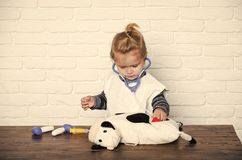 Child veterinarian examine toy animal with stethoscope. Boy play doctor with toy cow on white wall. Game, development, imagination. Future profession concept royalty free stock photos