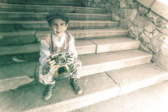 Child with vintage camera. Exterior stairs Stock Photo