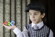 Child in vintage clothes hold letters a b c Stock Images