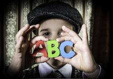 Child in vintage clothes hold letters a b c Stock Photo