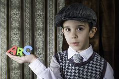 Child in vintage clothes hold letters a b c Stock Photos