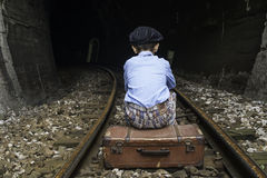 Child in vintage clothes sits on railway road Stock Photos