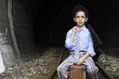 Child in vintage clothes sits on railway road Royalty Free Stock Photography