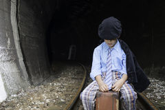 Child in vintage clothes sits on railway road Stock Image