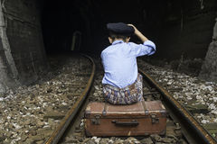Child in vintage clothes sits on railway road Royalty Free Stock Image