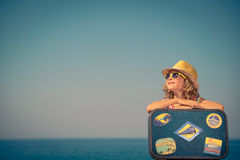 Child with vintage suitcase on summer vacation. Happy child with vintage suitcase. Kid having fun on summer vacation. Travel and adventure concept Stock Images