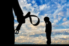 Child violence concept. Child violence. Silhouette father with a belt in his hand and a crying boy stock photo