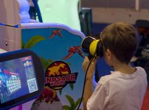 Virtual simulator. Child with a virtual reality device, in this context, virtual reality concerns the exporation of the world of dinosaurs, photo taken at enada royalty free stock photos