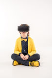 Child in virtual reality headset. Sitting on grey Royalty Free Stock Photos