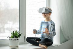 A child with a virtual reality headset is sitting at the table indoors at home. A girl exploring the world of virtual reality. Through video and games stock images