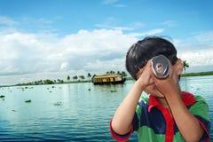 Child Vision. Boy having fun at Kumarakom lake resort, looking through the paper roll stock photos