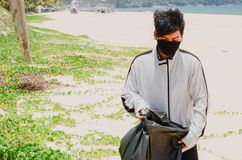 Child volunteer collecting garbage on beautiful beach at Karon Beach stock images