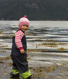 Child wading. Little girl in rain clothes wading in shallow water, lookin gat the camera Royalty Free Stock Image