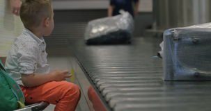 Child waiting at the baggage claim area. Little child sitting by the conveyor belt with luggage at the airport and watching people getting their bags stock footage