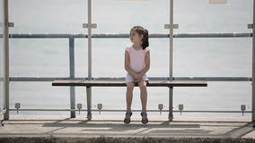 Child waiting for a bus at the bus stop looks around and misses.  stock footage