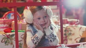 A child waiting for Christmas and Santa Claus looking out the window. Sweet girl in sweater and fur headphones holding her hands and waiting for Santa Claus. A stock video footage