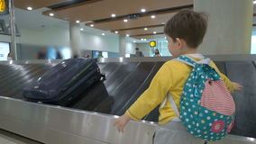 Child waiting for his luggage at conveyor belt in arrivals lounge of airport terminal building. Liittle child collecting his luggage at conveyor belt in arrivals stock video footage