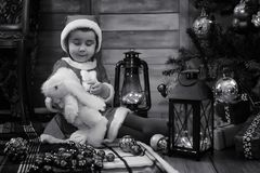 A child waiting for Santa Claus. A child sitting in front of a Christmas tree waiting for Santa Claus Royalty Free Stock Image