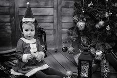 A child waiting for Santa Claus. A child sitting in front of a Christmas tree waiting for Santa Claus Royalty Free Stock Photos