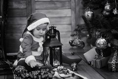 A child waiting for Santa Claus. A child sitting in front of a Christmas tree waiting for Santa Claus Royalty Free Stock Photo