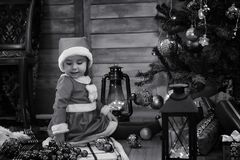 A child waiting for Santa Claus. A child sitting in front of a Christmas tree waiting for Santa Claus Stock Images
