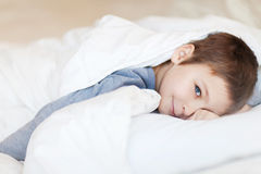 Child wakes up in the morning. Little boy wakes up in his bed Stock Photography