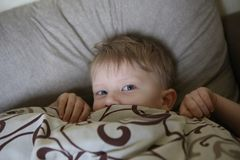 The child wakes up and peeks out from under the blankets stock photos