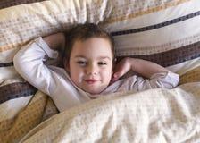 Child waking up in morning. Sleepy happy child lying in a bed, waking up in the morning Stock Image