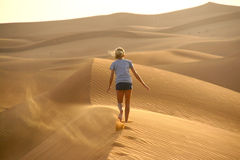 Child walking away on a sand dune royalty free stock photo