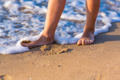 Child walking with bare feet along the seashore Royalty Free Stock Photo