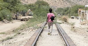 Child walking down railroad track in the desert of Ethiopia near royalty free stock photos