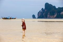 Child walking on fine sand through the water. Child enjoying the low tides, walking on fine sand through the water on a tropical beach. Fearless, intrepid and Royalty Free Stock Image