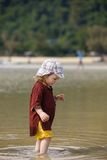 Child walking on fine sand through the water. Child enjoying the low tides, walking on fine sand through the water on a tropical beach. Fearless, intrepid and Royalty Free Stock Photos