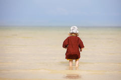 Child walking on fine sand through the water. Child enjoying the low tides, walking on fine sand through the water on a tropical beach. Fearless, intrepid and Royalty Free Stock Photo