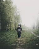 Child walking in foggy countryside