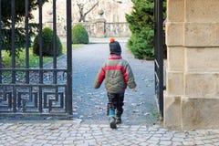 Child walking through a gate into a park or garden Royalty Free Stock Image