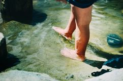 Child walking through low water barefoot outdoors. Close up, bod stock images