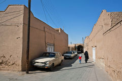 Child walking with mother through the street. YAZD, IRAN: Unidentified child walking with mother through the narrow street with clay houses. With population of royalty free stock photos