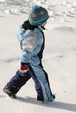 Child walking in snow Stock Images