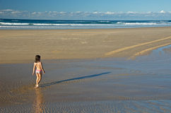 Child walking towards ocean stock photos