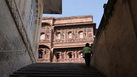Child walking up the stairs to indoor building of Mehrangarh fort. stock video footage