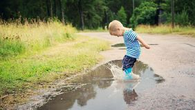 Child walking in wellies in puddle on rainy weather. Child walking in wellies and jumping in puddle on rainy weather. Boy under rain in summer outdoors stock images