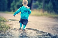 Child walking in wellies in puddle on rainy weather. Child walking in wellies and jumping in puddle on rainy weather. Boy under rain in summer outdoors stock photos