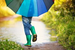 Child walking in wellies in puddle on rainy weather. Boy holding colourful umbrella under rain in summer Royalty Free Stock Image