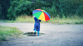Child walking in wellies in puddle on rainy weather. Boy holding colourful umbrella under rain in summer Stock Images