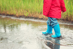 Child walking in wellies in puddle on rainy weather. Boy under rain in summer Royalty Free Stock Photography